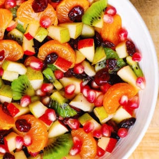 Winter Fruit Salad with Maple-Lime Dressing, with red apples, pears, clementine oranges (or mandarin oranges), kiwi fruit, dried cranberries, and pomegranate seeds