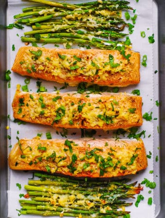 Parmesan Salmon and Asparagus on parchment paper on a baking sheet