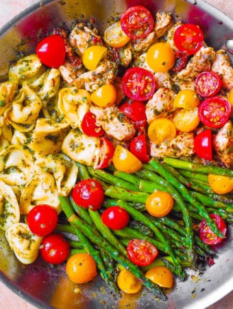 pesto chicken tortellini with cherry tomatoes and asparagus in a stainless steel skillet