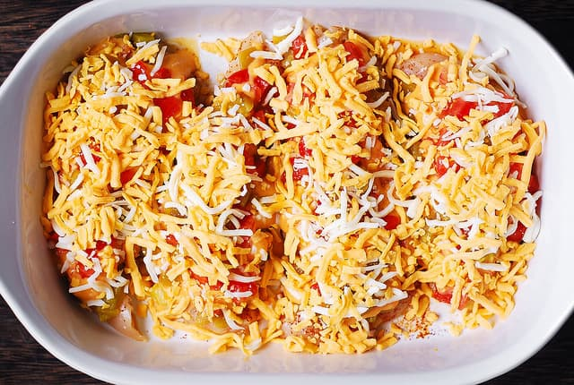 Top Queso smothered chicken with cheese in a baking dish