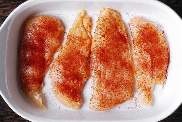 Add chili powder, cumin on top of chicken breasts in a casserole dish