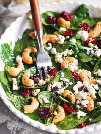 Cranberry Spinach Salad with Cashews and Goat Cheese and Lemon-Honey Poppy Seed Dressing in a white bowl, with a fork in the bowl