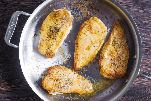 chicken coated in flour and seared in a skillet