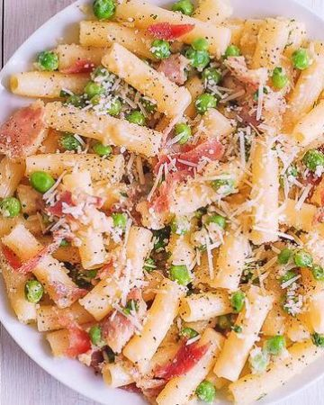 prosciutto pasta with peas on a white plate
