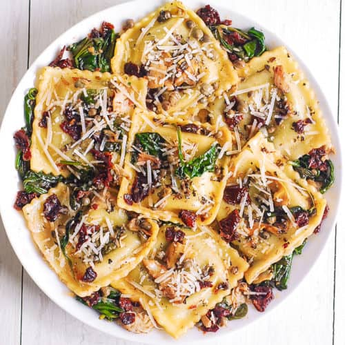 italian ravioli with sun-dried tomatoes artichokes capers and parmesan cheese on a white plate