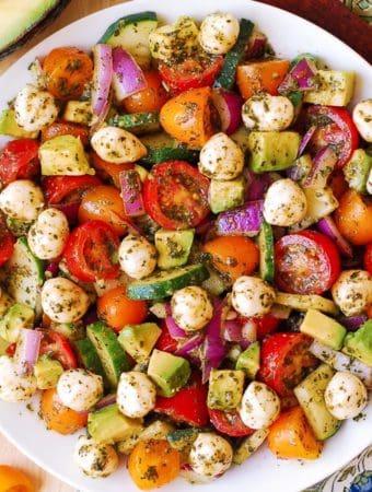 Avocado Salad with Tomatoes, Mozzarella, Basil Pesto on a white plate
