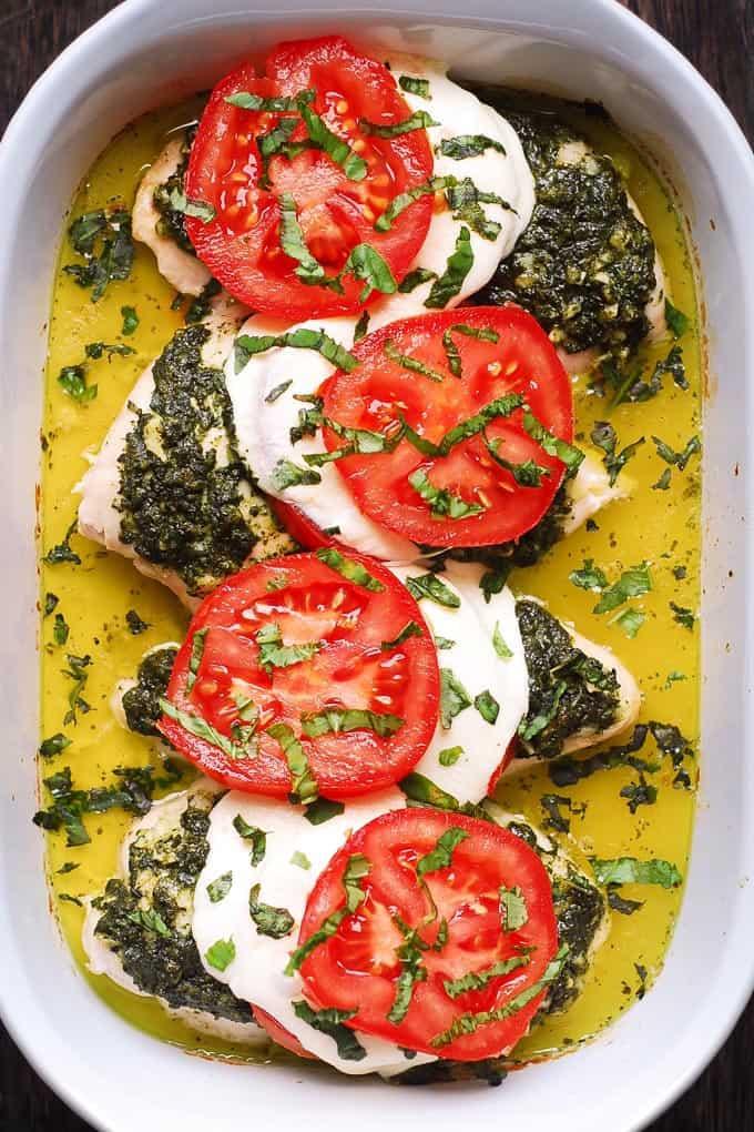 Basil Pesto Tomato Mozzarella Chicken Bake in a white casserole dish