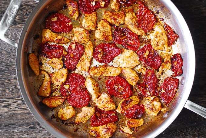 sliced chicken breast with sun-dried tomatoes, garlic in a large skillet