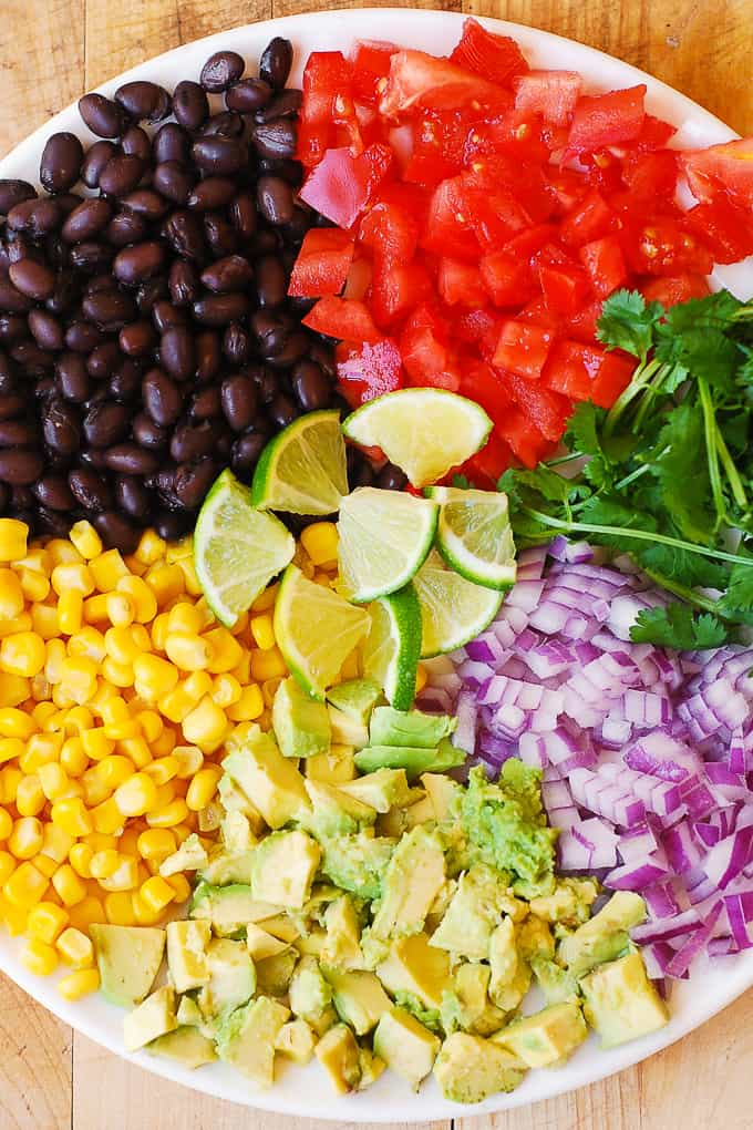 homemade guacamole with avocados, black beans, corn, tomatoes, cilantro, lime juice