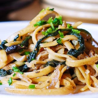 mushroom spinach pasta with caramelized onions on a white plate