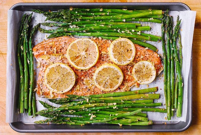 baked rainbow trout and asparagus with lemon on parchment paper lined sheet pan