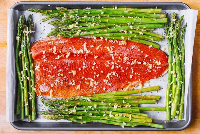 salt and pepper and minced garlic sprinkled over the rainbow trout fillet and asparagus on sheet pan