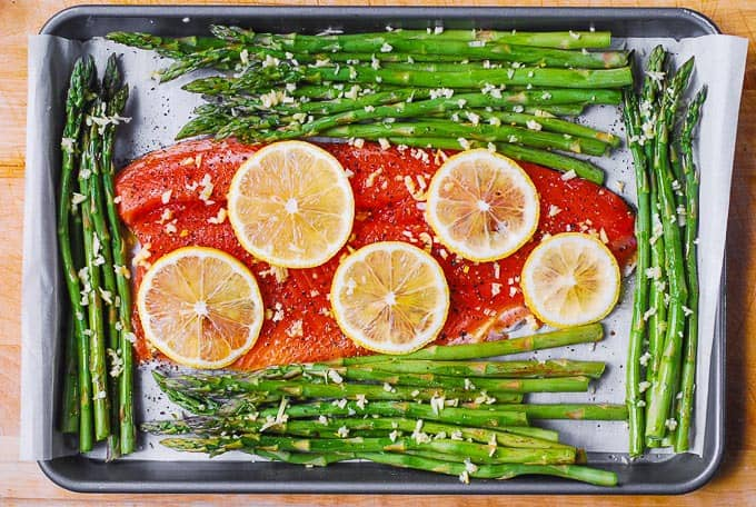 lemon slices on top of rainbow trout fillet with asparagus on sheet pan