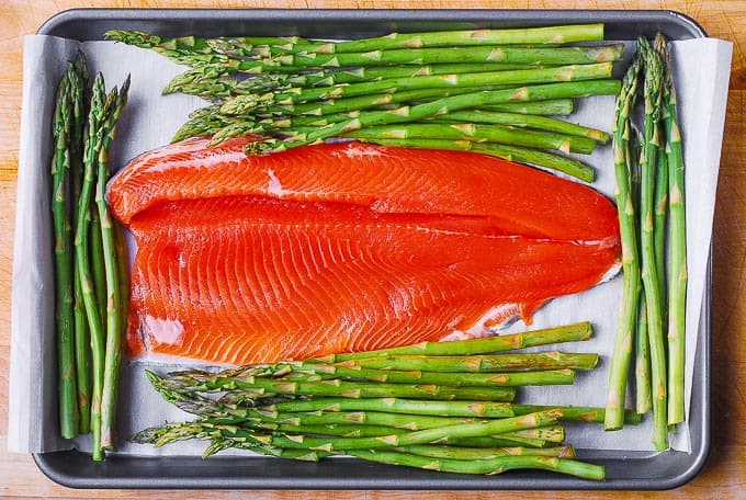 rainbow trout fillet skin side down and asparagus on parchment paper lined sheet pan