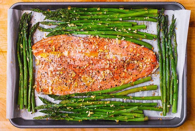 cooked rainbow trout with asparagus on parchment paper lined sheet pan