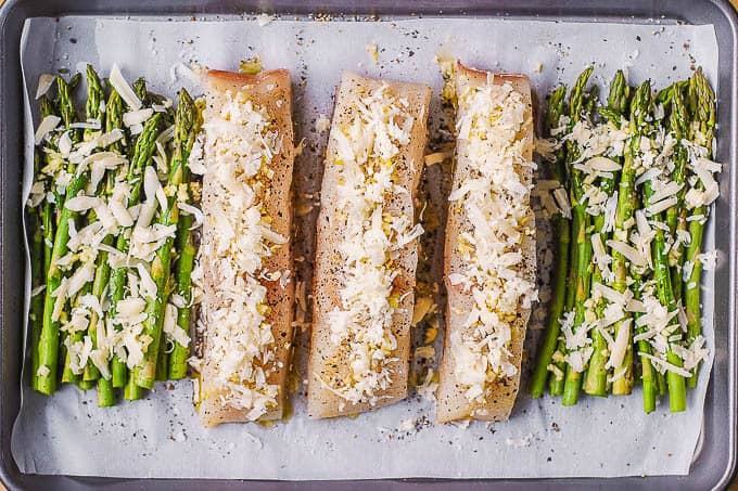halibut and asparagus with garlic and Parmesan cheese on a baking sheet