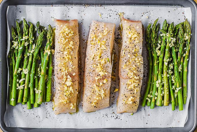 halibut and asparagus with garlic and olive oil on baking sheet