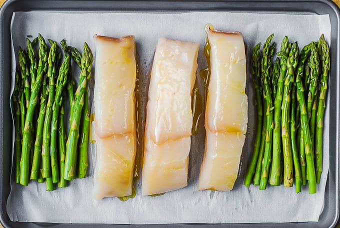halibut and asparagus with olive oil on top on baking sheet