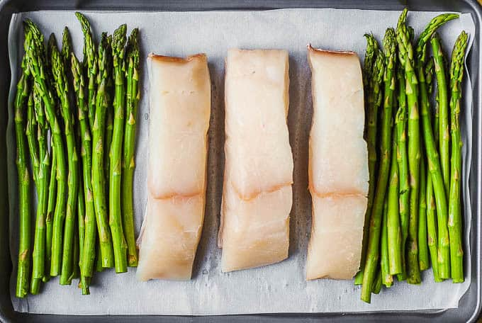 halibut and asparagus on parchment lined baking sheet