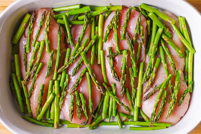 chicken breasts with asparagus in a casserole dish