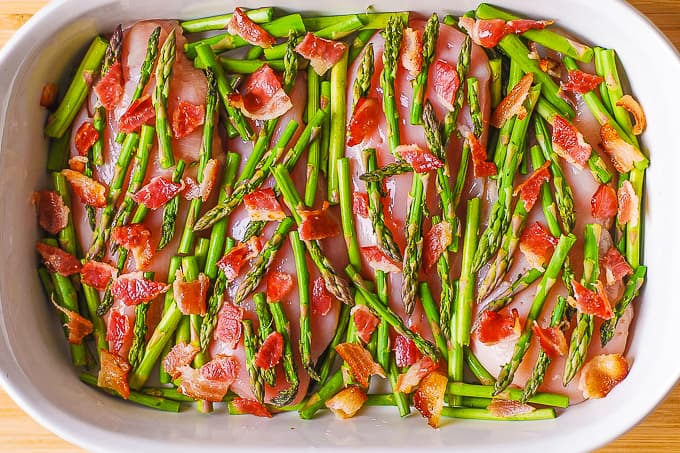 chicken breasts, asparagus, bacon in a casserole dish