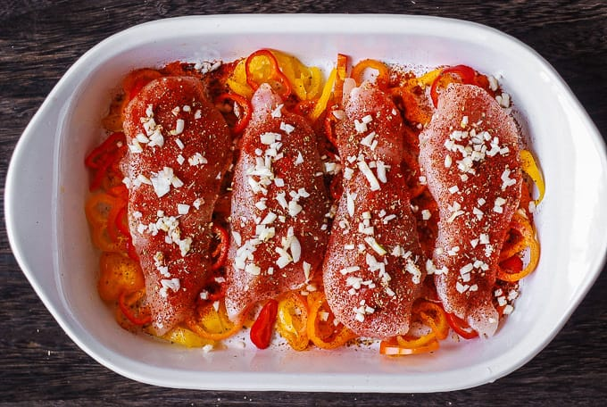 garlic on top of Cajun chicken breasts with bell peppers in a casserole dish