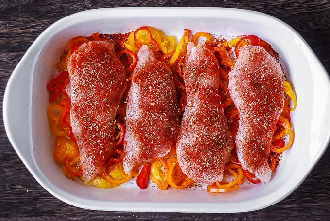 chicken seasoned with Cajun spice on top of bell peppers in a casserole dish