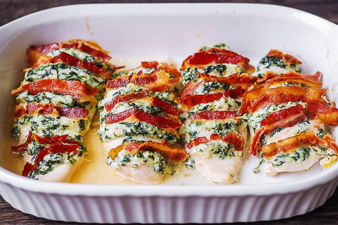 hasselback chicken stuffed with spinach dip, mozzarella, parmesan, cream cheese, bacon in casserole dish
