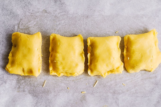 folding the edges of the chicken puff pastry rectangles on baking sheet