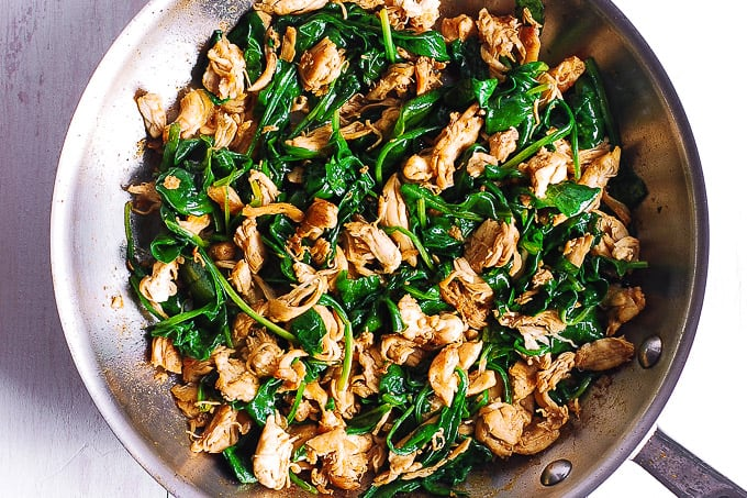 cooked chicken seasoned with paprika with spinach in a skillet
