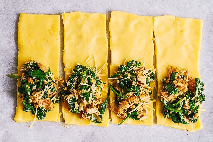 puff pastry rectangles with spinach and chicken filling on baking sheet