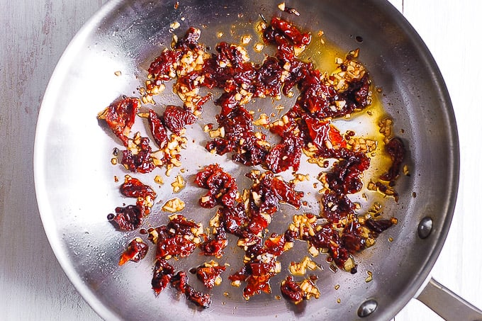 cooking garlic and sun-dried tomatoes in olive oil in a skillet