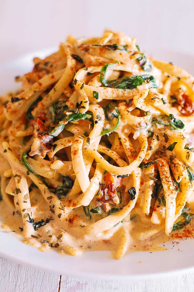 linguine with spinach and sun-dried tomato cream sauce on a plate
