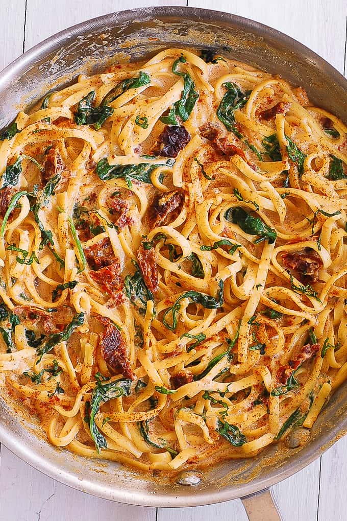 linguine with spinach and sun-dried tomato cream sauce in a skillet