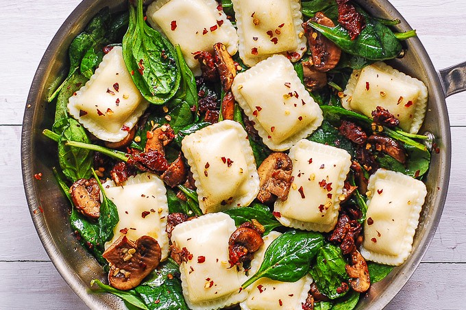 cheese ravioli with mushrooms, spinach, sun-dried tomatoes, garlic in a skillet