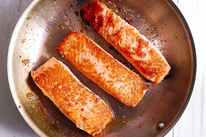 seared salmon fillets in a skillet