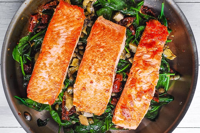 salmon on top of sauteed spinach with sun-dried tomatoes, garlic, artichokes, capers