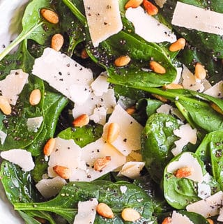 simple spinach salad with pine nuts and shaved parmesan cheese