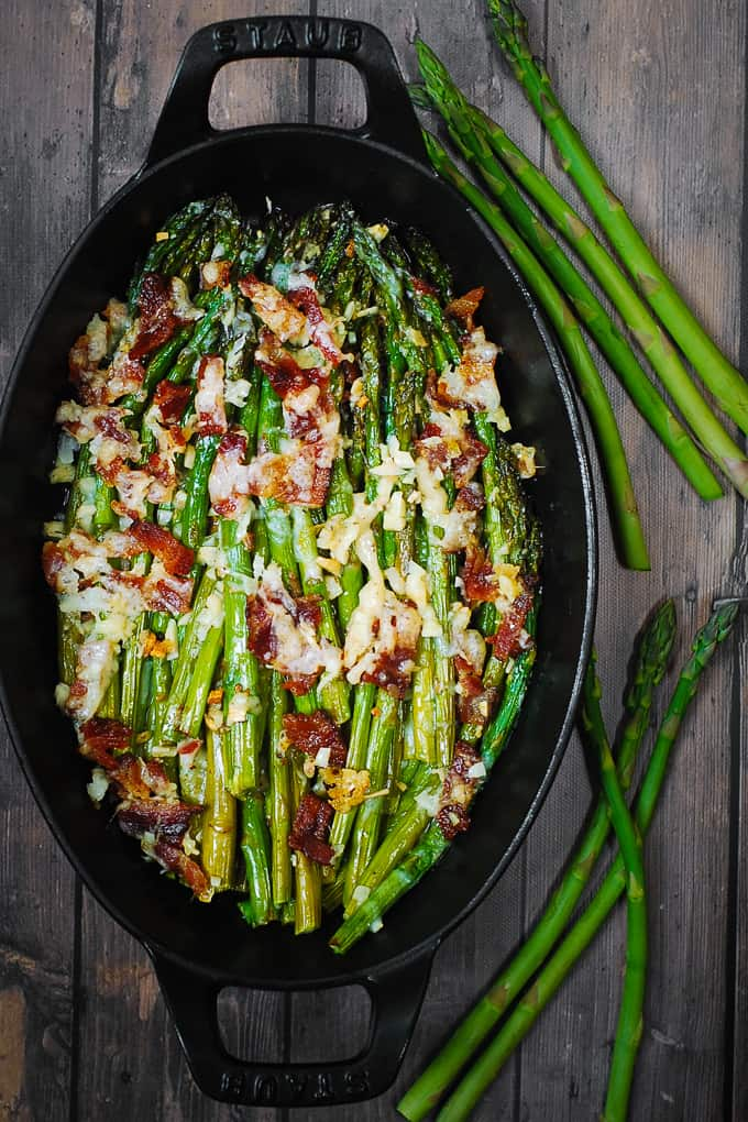 Cheesy Baked Asparagus with Bacon in a cast-iron dish
