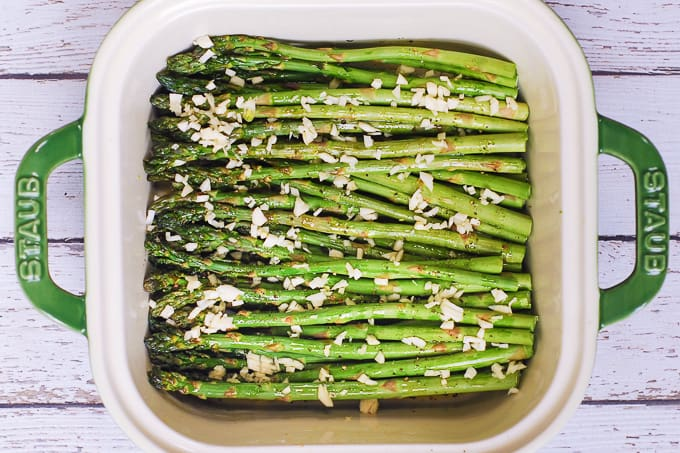 asparagus seasoned with salt and pepper, drizzled with olive oil, topped with minced garlic in a baking dish