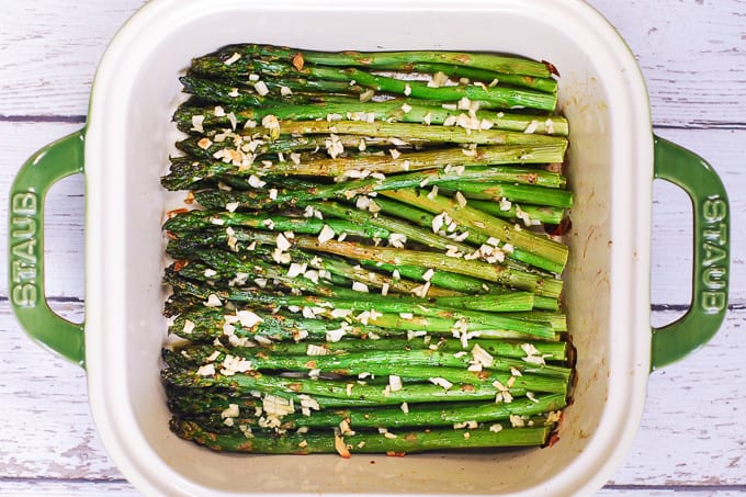 roasted asparagus seasoned with salt and peppers, drizzled with olive oil, topped with minced garlic in a baking dish