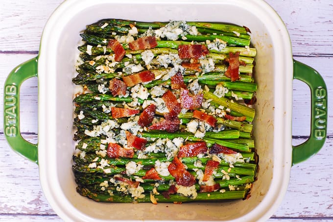 chopped cooked bacon on top of asparagus in a baking dish