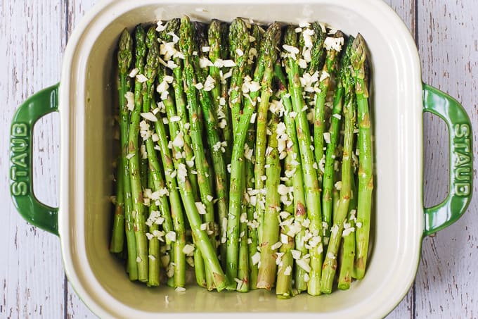 Asparagus drizzled with olive oil, seasoned with salt and pepper, and topped with fresh minced garlic in a white casserole dish