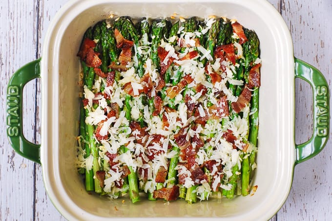 Asparagus with shredded cheese and cooked bacon in a casserole dish