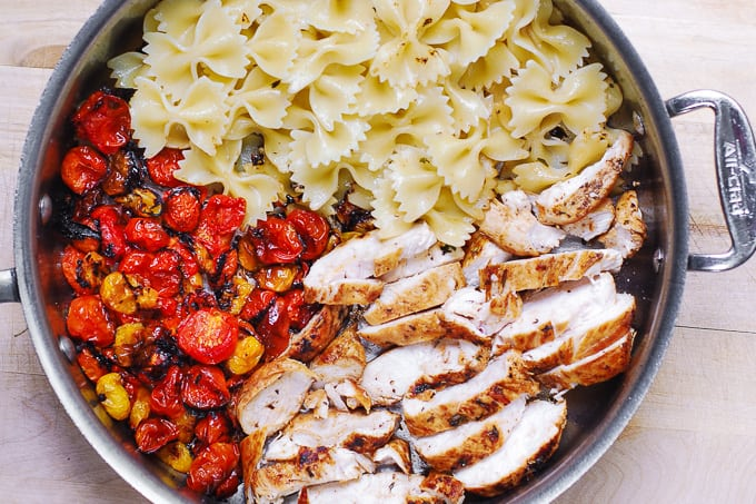 sliced cooked chicken breasts, roasted tomatoes, and cooked bow-tie pasta in a large skillet
