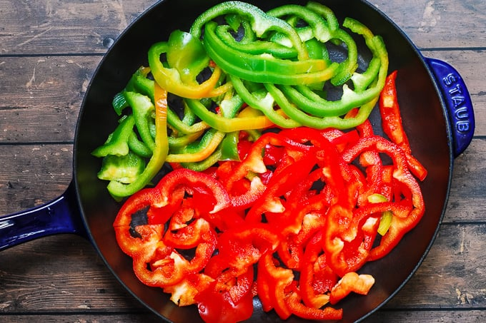 sliced green and red bell peppers in a cast iron skillet