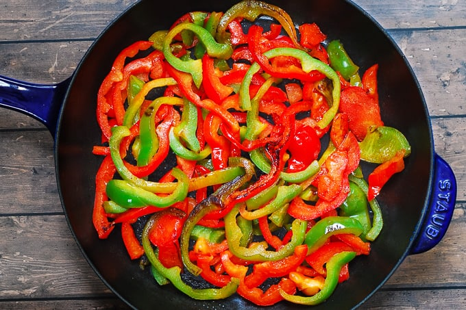 seared red and green bell peppers in a cast iron skillet