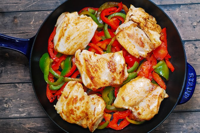 seared chicken thighs on top of cooked bell peppers in a cast iron skillet