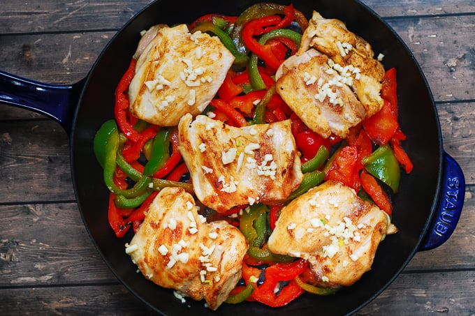 minced garlic on top of seared skinless, boneless chicken thighs on top of cooked bell peppers in a cast iron skillet