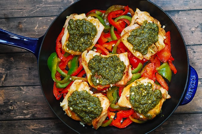 basil pesto over chicken thighs in a cast iron skillet